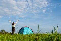 Handelsresande som har att campa med tältet på fält royaltyfri foto