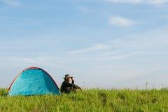 Handelsresande som har att campa med tältet på gräsfält royaltyfri fotografi