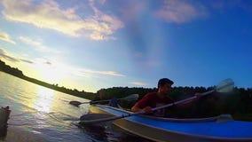Handelsresande som kayaking på solnedgången, handlingkamera som är undervattens-, långsam-mo stock video