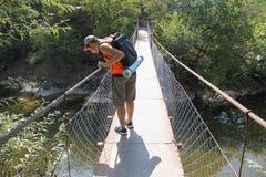 Handelsresande som ser naturen från upphängningbron Den aktiva och sunda livsstilen på sommarsemester och helg turnerar Arkivfoto