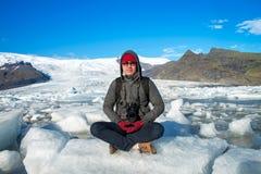 Handelsresande som sitter p? liten ishylla och g?r meditation royaltyfria bilder