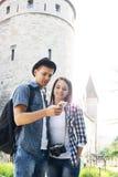Handelsresande som tar selfie med ett medeltida torn på bakgrunden royaltyfria bilder