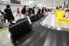 Handelsresande som väntar på bagage från transportbandet fotografering för bildbyråer