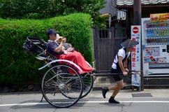 Handelsresandebruksrickshawen för turnerar runt om arashiyamastad Arkivfoto