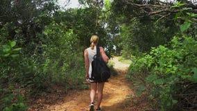 Handelsresandeflicka med en ryggsäck som promenerar en slinga på en tropisk ö, hållande ögonen på skogträd och havet härligt stock video