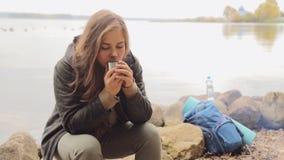 Handelsresandeflicka som dricker te från termoskoppen, utomhus lager videofilmer