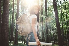Handelsresandehipsterkvinnan med ryggsäcken och hatten rymmer, i handlägeöversikten och sökande som är riktnings bland träd i sko royaltyfria foton