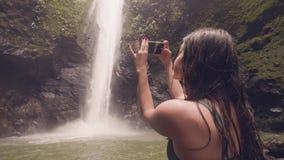 Handelsresandekvinna som använder smartphonen för fotoet som plaskar vattenfallet i videoen för skytte för djungelskogkvinna den  arkivfilmer