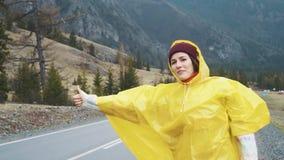 Handelsresandekvinna som liftar på en molnigt väg och gå Ung lycklig fotvandrarekvinna som söker efter en ritt för att starta a lager videofilmer