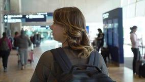 Handelsresandekvinnan går på flygplatsen för avvikelse Flicka med ryggsäcken på flygplatsen lager videofilmer