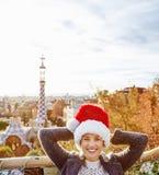 Handelsresandekvinnan i jultomtenhatt på Guell parkerar att koppla av på bänk Arkivbild