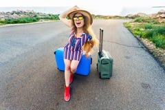 Handelsresandekvinnan som bär en klänning och en hatt, sitter på den blåa resväskan på vägen och skrattar Royaltyfri Bild