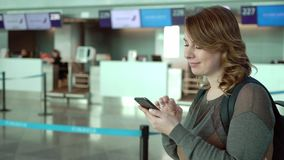 Handelsresandekvinnan står på flygplatsen för avvikelse Flicka med ryggsäcken på flygplatsen lager videofilmer