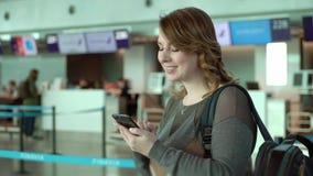 Handelsresandekvinnan står på flygplatsen för avvikelse Flicka med ryggsäcken på flygplatsen arkivfilmer