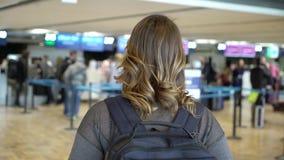 Handelsresandekvinnan st?r p? flygplatsen f?r avvikelse Flicka med ryggs?cken p? flygplatsen stock video
