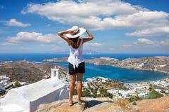 Handelsresandekvinnan tycker om sikten till den härliga ön av Ios, Cyclades, Grekland fotografering för bildbyråer
