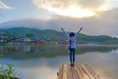 Handelsresandelivsstilkvinnan som känner segerrik fasadbeklädnad på bron i sjön, säsongvinter i soluppgångmorgonen, kopplar av oc fotografering för bildbyråer