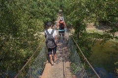 Handelsresandelopp på den konstgjorda körbanan av upphängningbron Aktiva fotvandrare Aktiv och sund livsstil på sommarsemester Arkivfoto