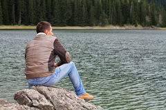 Handelsresandeman som tycker om bergsjösikt Man som ser horisonten, ensamhetbegrepp Arkivfoto