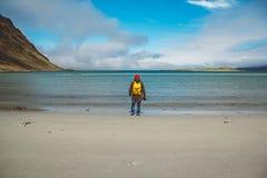 Handelsresanden är en yrkesmässig fotograf som tar över landskapfotolandskapet Bära en gul ryggsäck i ett rött arkivfoton