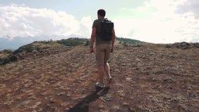 Handelsresanden för den unga mannen klättrar berget stock video