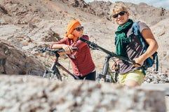 Handelsresanden för två cyklister är i berg Arkivbild