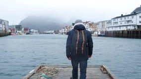 Handelsresanden går på en träpir Iklätt ett omslag och en stucken hatt och ryggsäck tillbaka sikt Norge Reine stock video