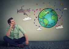 Handelsresandesammanträde för ung man på golvet som runt om världen tänker om en fantastisk tur arkivbild