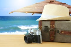 handelsresandetappningbagage, kamera och fedorahatt över trätabellen i framdel av havslandskapet Ferie- och semesterbegrepp royaltyfri fotografi