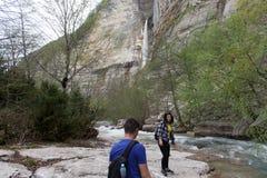 Handelsresandeung flicka och män som går i vattenfallkanjon Loppaffärsföretag och fotvandraaktivitet Arkivbild