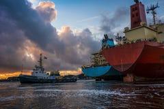 Handelsschiffe sind mit Liegeplatzoperationen während des Sonnenuntergangs im Hafen beschäftigt Lizenzfreie Stockfotos