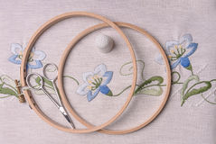 Handemade embroidery. The cloth, thimble, scissors, embroidery hoop. Blue flowers Stock Photos