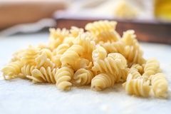 Handemade pasta closely on table. Hand made Italian pasta fusilli uncooked on kitchen table. macro stock photo