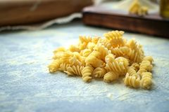 Handemade pasta closely on table. Hand made pasta fusilli uncooked on blue table in kitchen. macro royalty free stock photos