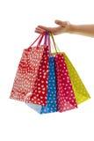 Handen är hållande färgrika shoppingpåsar Royaltyfri Bild