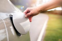 Handen öppnar locket för olja för bil` s för att tanka Royaltyfria Bilder