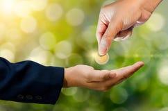 Handen överför myntet som grön bokehbakgrund ger pengar arkivfoton