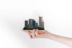 Handen använder en smartphone eller en minnestavla och att söka efter fastighet- eller framtidsinvestering isolerat framförande f Arkivfoto
