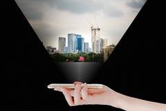 Handen använder en smartphone eller en minnestavla och att söka efter fastighet- eller framtidsinvestering isolerat framförande f Royaltyfri Fotografi