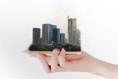 Handen använder en smartphone eller en minnestavla som söker efter fastigheten isolerat framförande för begrepp 3d investering Arkivbilder