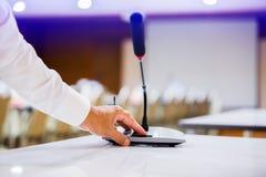 Handen av affärsmannen trycker på för att driva på trådlösa konferensmikrofoner i en mötesrum royaltyfria bilder