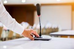 Handen av affärsmannen trycker på för att driva på trådlösa konferensmikrofoner i en mötesrum fotografering för bildbyråer
