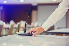 Handen av affärsmannen trycker på för att driva på trådlösa konferensmikrofoner i en mötesrum arkivfoto