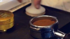 Handen av att använda för barista fifflar för att trycka på jordkaffe in i portafilter för att göra espressokaffe stock video