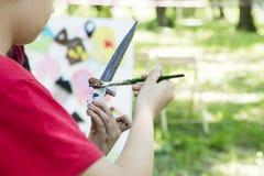 Handen av barnet med en borste målar en leksak Hand för barn` s med tofsen i bilden royaltyfri foto