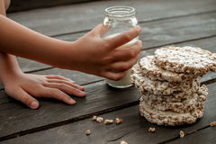 Handen av barnet tar mjölkar hem smaklig knäckebröd på träbakgrundstabellen Arkivfoto