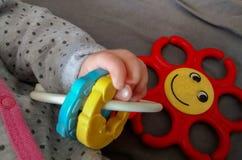 Handen av behandla som ett barn att lägga på baksida, hållande leksak Arkivfoton