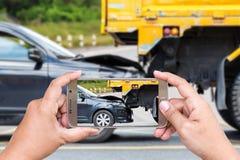 Handen av den hållande smartphonen för kvinnan och tar fotoet av bilolyckan Royaltyfria Bilder