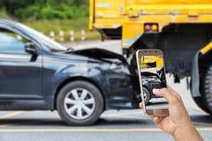 Handen av den hållande smartphonen för kvinnan och tar fotoet av bilolyckan Fotografering för Bildbyråer