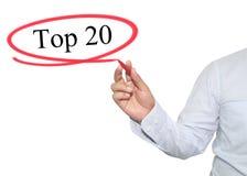 Handen av den isolerade mannen skriver text topp 20 med svart färg på vit Royaltyfri Foto